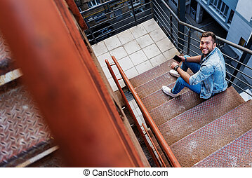 Cheerful man with phone on staircase
