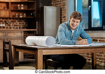 Cheerful man working on the creation of blueprint