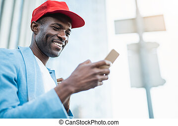 Cheerful man working with gadget