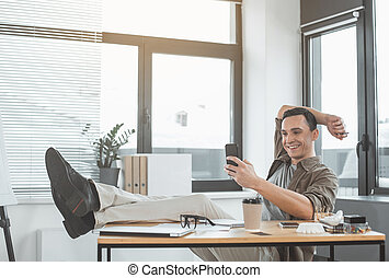 Cheerful man working with phone