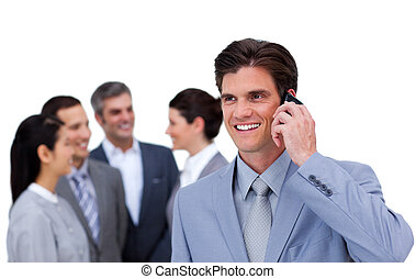 Cheerful manager on phone standig in front of his team