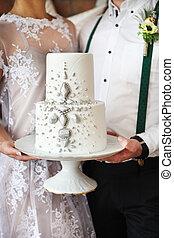 Cheerful married couple holding wedding cake