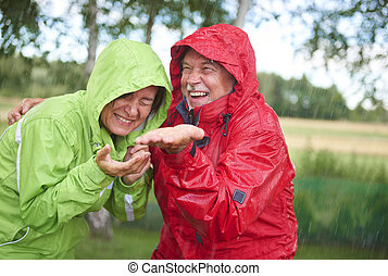 Cheerful married having a fun in rain