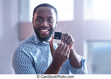 Cheerful mature African American man demonstrating engagement ring