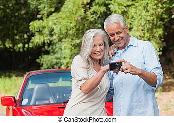 Cheerful mature couple looking at pictures on their camera