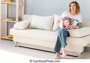 Cheerful mature lady with magazine at home