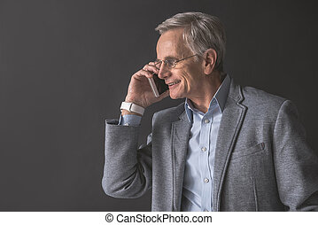 Cheerful mature male speaking by phone