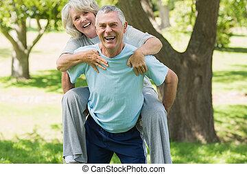 Cheerful mature man carrying woman at park