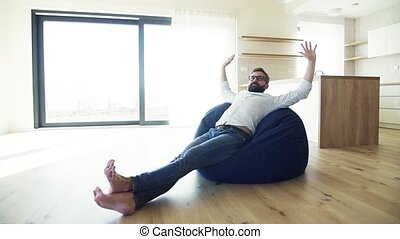 Cheerful mature man jsitting on bean bag in unfurnished house, moving in new home concept. Slow motion.