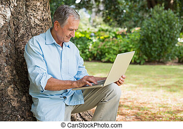 Cheerful mature man sitting on tree