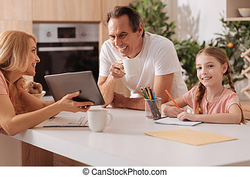 Cheerful mature mother using gadget with family at home