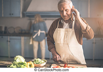 Cheerful mature pensioner enjoying melody in kitchen