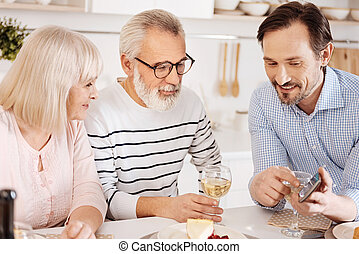 Cheerful mature son enjoying family dinner at home