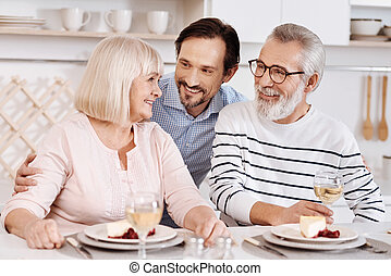 Cheerful mature son hugging elderly parents at home