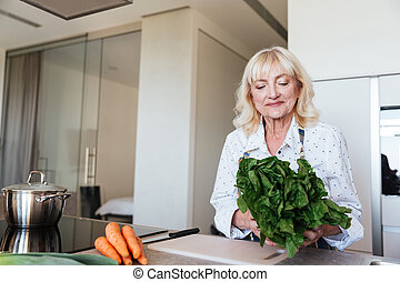 Cheerful mature woman at home cooking in kitchen.