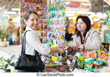 cheerful mature woman buys seeds in gardener market. Focus ...