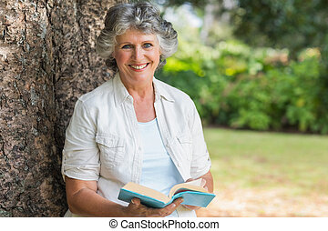 Cheerful mature woman holding book sitting on tree trunk