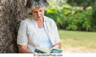 Cheerful mature woman reading book sitting on tree trunk