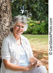 Cheerful mature woman sitting on tree trunk