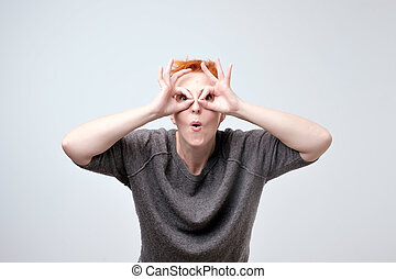 Cheerful mature woman with red hair holding fingers near eyes like glasses