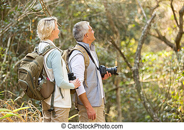 middle aged couple bird watching in forest - cheerful middle...
