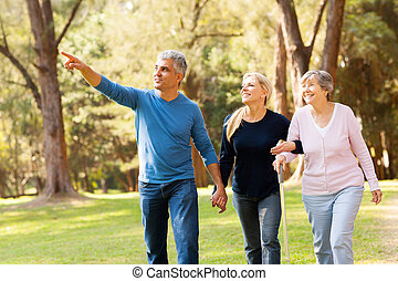 middle aged couple taking elderly mother for a walk