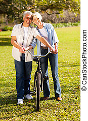 middle aged couple walking a bike