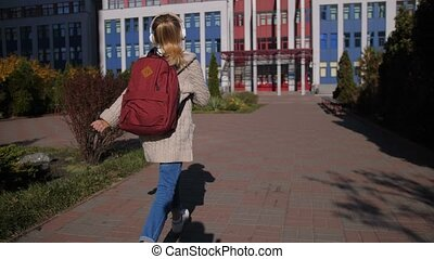Cheerful middle school girl running to lessons