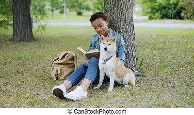 Cheerful mixed race girl dog owner is reading book and stroking her cute puppy sitting on grass in park on summer day. Backpack, green lawn and trees are visible.
