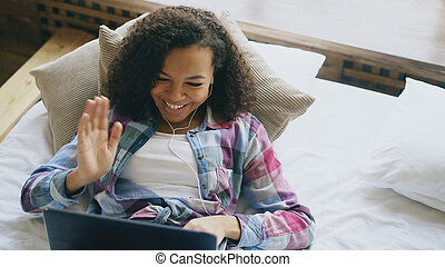 Cheerful mixed race girl having video chat with friends using laptop camera while lying on bed