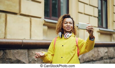 Cheerful mixed race girl is making video call, speaking and...