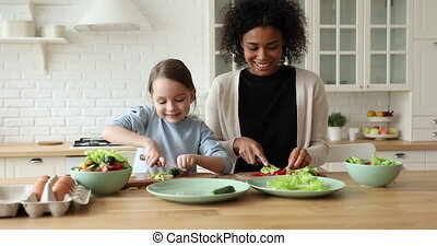 Cheerful mixed-race mom and daughter giving high five in kitchen