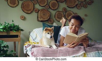 Cheerful mixed race teenage girl is reading book enjoying...