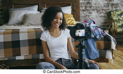 Cheerful mixed race woman recording video blog about her wardrobe for travel with dslr camera at home