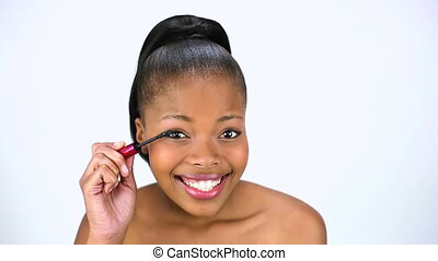 Cheerful model applying mascara