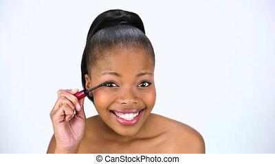 Cheerful model applying mascara while posing on white...