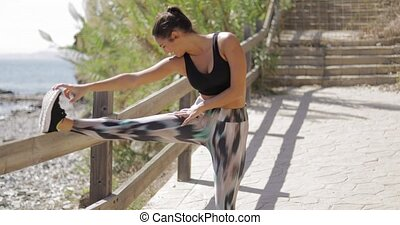 Confident young woman in sportswear posing cheerfully on waterfront of ocean and working out alone stretching muscles.