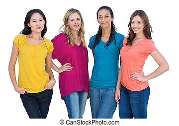 Cheerful models posing with hands on hips on white ...