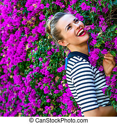 cheerful modern woman near colorful magenta flowers bed -...