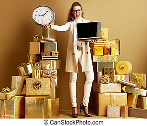 cheerful modern woman showing laptop blank screen and clock
