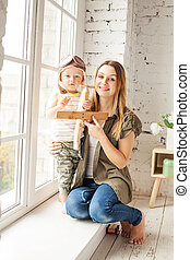 Cheerful Mom and her Son are Playing Wooden Handmade Plane Toys. Happy Loving Family