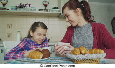 Cheerful mother and cute daughter having breakfast eating...