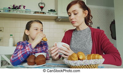 Cheerful mother and cute daughter having breakfast eating muffins and croissants talking at home in modern kitchen. Family, food, home and people concept
