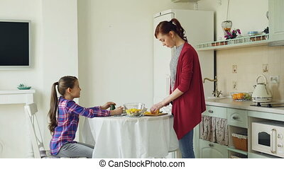 Cheerful mother and cute daughter talking and laughing in modern kitchen. Mom cooking meal cutting vegetables. Family, food, home and people concept