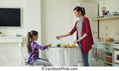 Cheerful mother and cute daughter talking cheerfully in modern kitchen. Mom cooking dinner when girl comes. Family, food, home and people concept