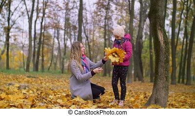 Cheerful mother and daughter enjoying fall season - Positive...