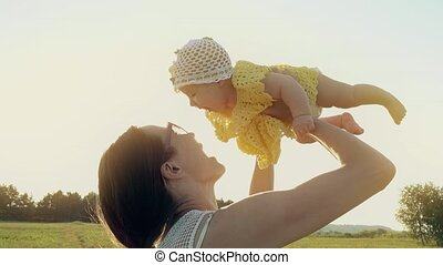 Cheerful mother and her baby girl on summer field in the evening