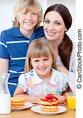Cheerful mother and her children eating waffles with strawberries in the kitchen