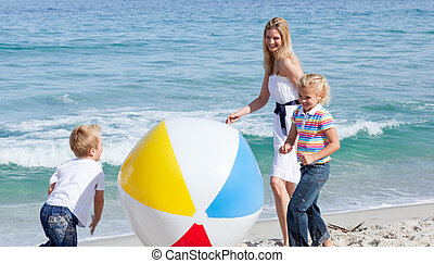 Cheerful mother and her children playing with a ball