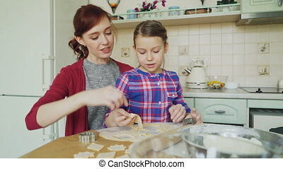 Cheerful mother and little cute daughter talking and making cookies together using bakery forms cropping dough while sitting in modern kitchen at home. Family, food and people concept